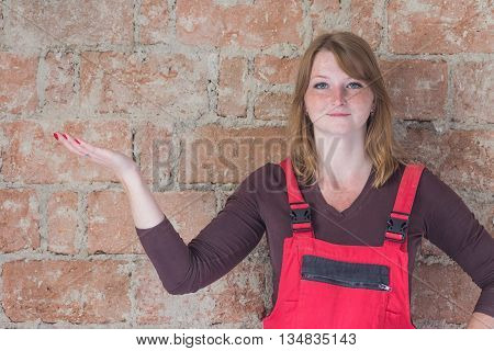 Smiling redhead young woman dressed in red overall is standing in front of an old brick wall. Woman is looking at the camera. Place for your text is in the left half of the image over the open hand of the woman.