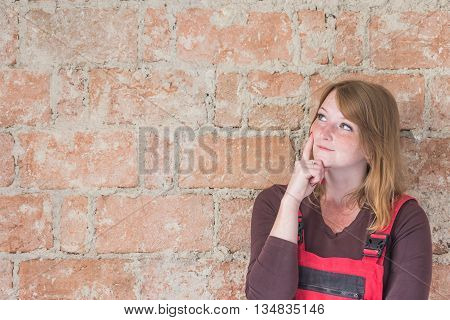 Smiling redhead young woman dressed in red overall is thinking in front of an old brick wall. Woman is looking at the wall. Place for your text is in the left half of the image.