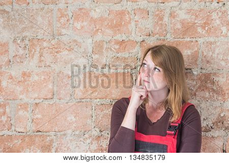 Pensive redhead young woman dressed in red overall is standing in front of an old brick wall. Woman is looking at the wall. Place for your text is in the left half of the image.