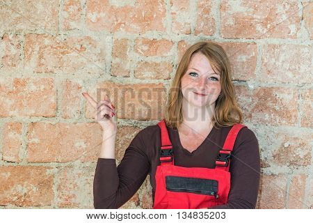 Smiling redhead young woman dressed in red overall is standing in front of an old brick wall. Woman is looking at the camera and is pointing the finger at the wall. Place for your text is in the left half of the image.
