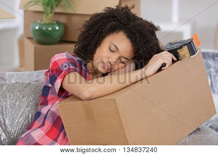 young woman sleeping on packing cases