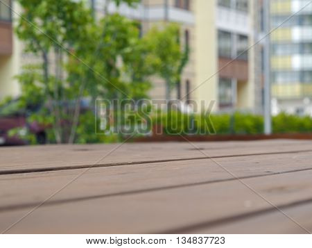 Wooden boards against a blurred background - city building green trees the car