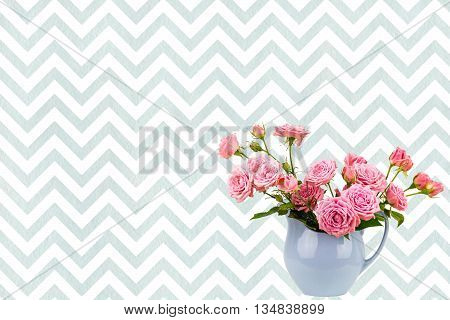 Pink flowers in blue jug. Roses in jug.