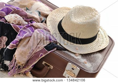 straw hat on a suitcase with sarong isolated on white background