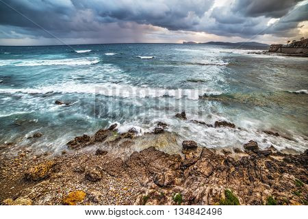 Alghero coastline under a dramatic sky at sunset Italy
