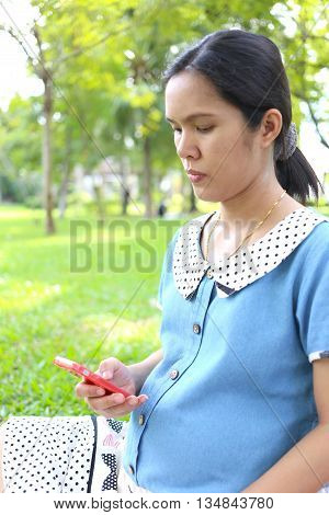 Pregnant women using smartphones to search for information about health care in the public park.