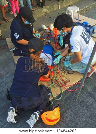 Dumaguete, Philippines - 30 March, 2016: Rescue and medic help to the victim of a fire. Rescue operation during a fire