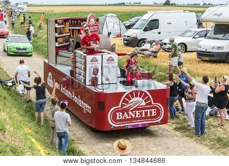 Quievy,France - July 07 2015: Banette vehicle during the passing of the Publicity Caravan on a cobblestone road in the stage 4 of Le Tour de France on July 7 2015 in Quievy France. Banette is the leading brand for the artisan bread in France.