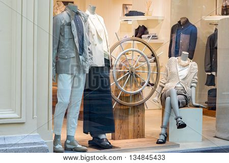 Moscow Russia - June 14 2016: The window of Brunelli Cucinelli store. Boutique window with dressed mannequins and steering wheel
