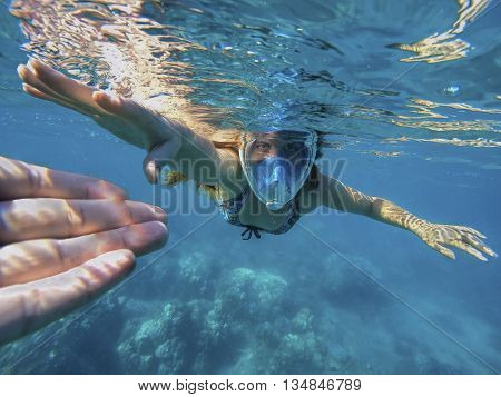 Beautiful woman under water before dive to coral reef, woman snorkeling in blue mask