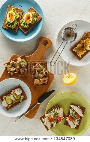 Healthy sandwiches with various fillings on crisp rye bread top view.