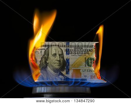 Dollar bill on fire in gas burner flame. Gas burner burning one hundred dollar bill.