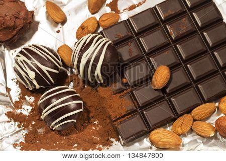 Chocolate truffles almonds and chocolate bar on aluminum foil