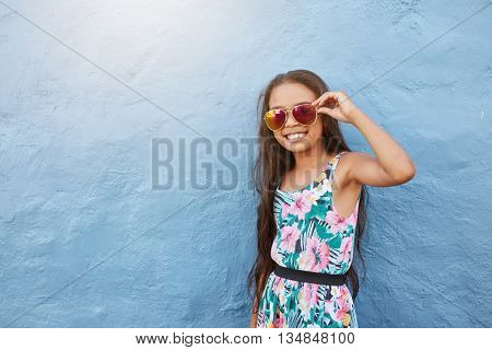 Portrait of stylish little girl with sunglasses. Preteen girl posing against blue wall with copy space.