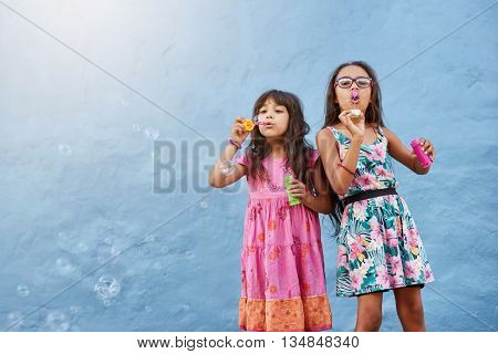Portrait of adorable little girls blowing soap bubbles against blue wall. Two young girls playing together.