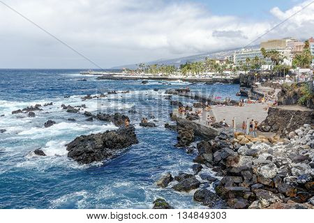 Puerto de la Cruz Spain - August 16 2015: Tourists enjoy the good weather and relax on the beach of San Telmo in the Atlantic Ocean Puerto de la Cruz Tenerife Canary Islands Spain