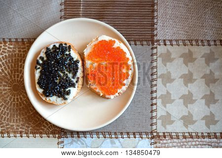 Sandwiches with red and black caviar and butter on a plate