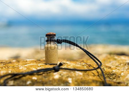 Vial with white sand like memory about tropical vacation. Sea and blue sky background