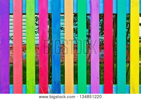 Fence from colourful rows of painted wood planks