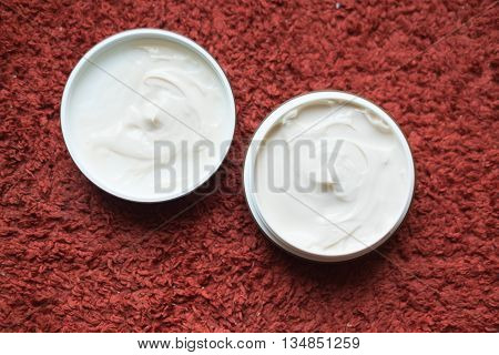 Hair wax and clay in tubs on red background