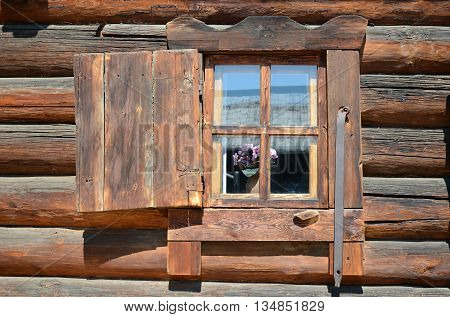 The wooden window with shutter. Old log house. Russia
