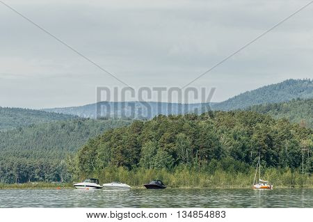 motor boats and yacht stand at shore of lake on background of mountains and forest