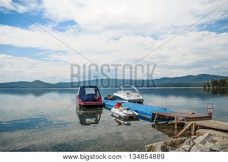motor boats are on dock at lake. blue sky mountains and forest