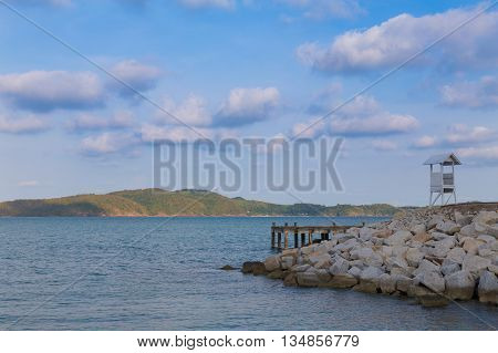 White lifeguard over rocky walking path and ocean skyline and island, natural landscape background