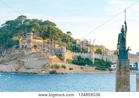 Statue of Minerva on the enbankment, Fortress and Badia de Tossa bay in Tossa de Mar on Costa Brava at summer sunset, Catalunya, Spain.