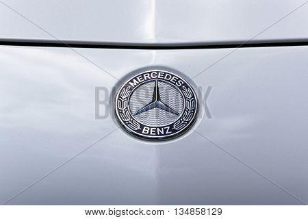 TURIN, ITALY - JUNE 13, 2015: A Mercedes Benz logo on a light grey car body