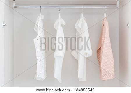 Shirts Hanging On Rail In White Wooden Wardrobe