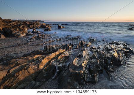 Beautiful Vibrant Sunset Landscape Image Of Calm Sea Against Rocky Shoreline