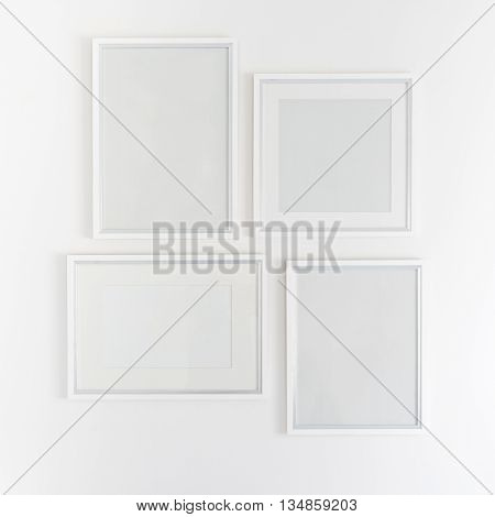 white blank picture frames hanging on white wall