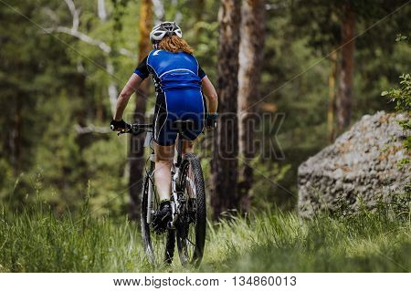 rear view of a female cyclist riding on green grass in forest