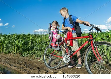 Sibling teenage boy is cycling with his little sibling sister on baby bike seat on farm corn field dirt road