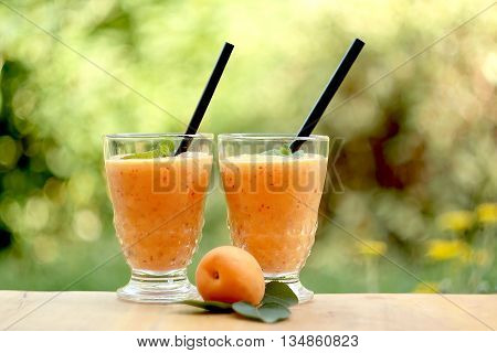 Two glasses of apricot smoothie and fresh apricot