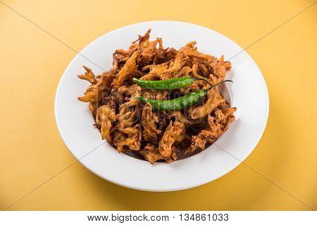 Onion Bhajis or onion pakora or kanda bhaji served with fried green chilli