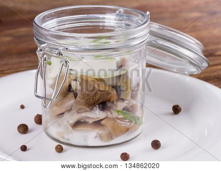 Salted milk mushrooms in a glass jar with cream sauce