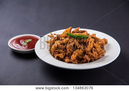 onion bhaji or kanda bhaji or bhaje or onion pakora or pakoda, fried Indian snack served with tomato ketchup