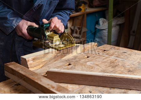 Carpenter Working On A Wooden Boards In His Workshop