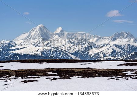 Scenic view with the beautiful mountain peaks with snow and glaciers slopes covered with snow and sparse brown vegetation against a blue sky