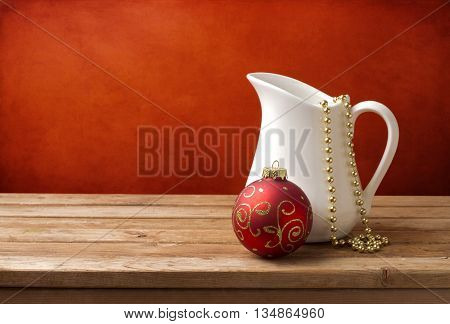 Christmas background with white jug and christmas ornament on wooden table over red grunge background