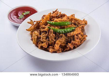 onion bhaji or kanda bhaji or bhaje or onion pakora or pakoda, fried Indian snack served with tomato ketchup