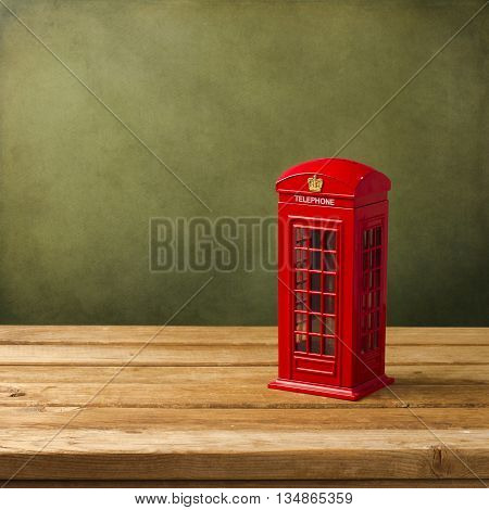 London telephone booth moneybox on wooden table against grunge background