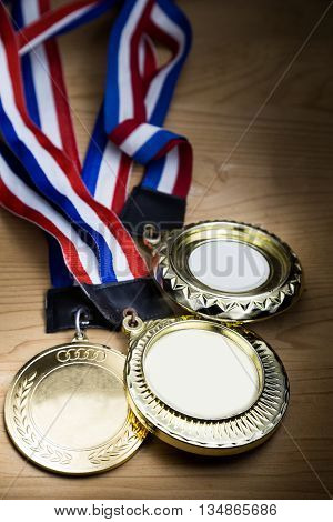 Three generic sporting event gold medal with red and blue ribbon on wooden surface against ray of lights. Fine art rendition.