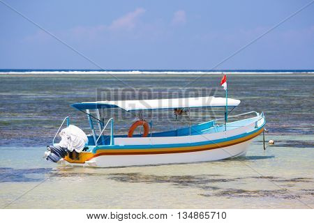 A Balinese fishing boat moored on a Sanur beach in Bali, Indonesia