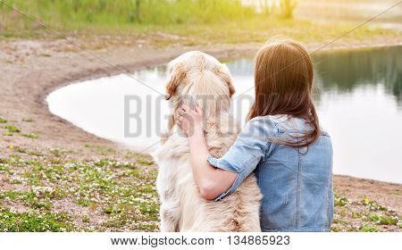 Silhouette Golden Retriever owner and dog sitting on the grass near a river in sunny summer day