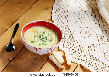 Cream soup, spoon and bread croutons on a table