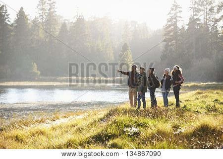Five friends walking near a lake take in view, one points