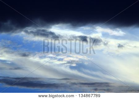 Evening landscape with beautiful darl clouds on the sky with sun beams